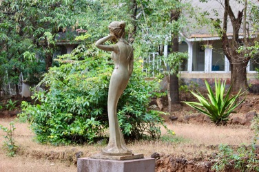 A sculpture in the garden of an abandoned bungalow